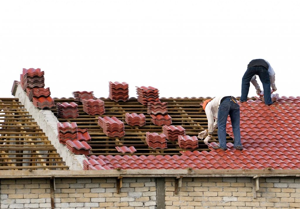 workers are installing house roof tile