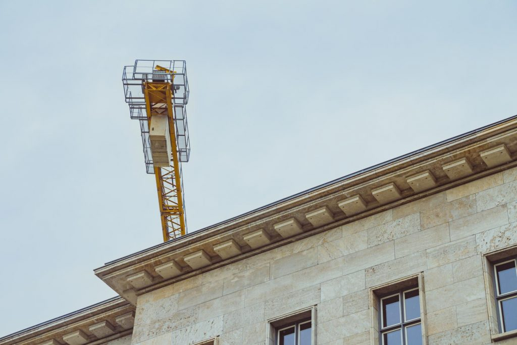 a yellow crane on the commercial roof