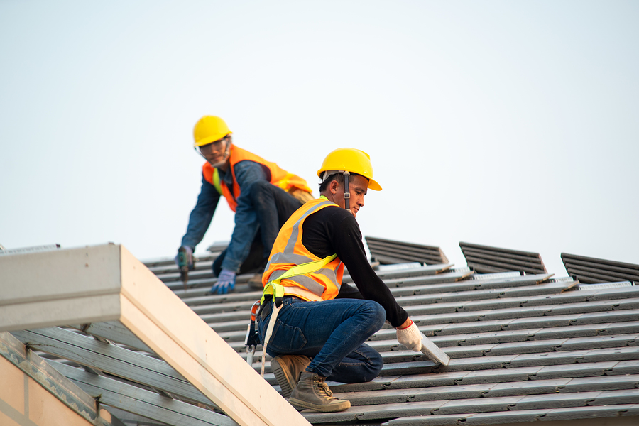 construction worker using nail gun to install new roof on top roof