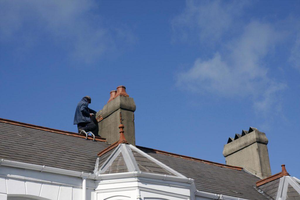 man repairing the roof beside the chimney